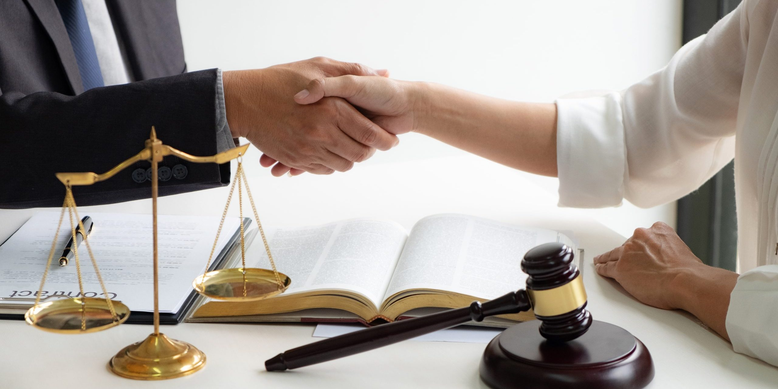 lawyer consultant with client shaking hands together with contract agreement.